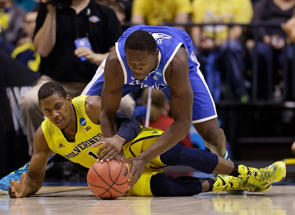 . Michigan\'s Glenn Robinson III (1) and Kentucky\'s Julius Randle go after a loose ball during the second half of an NCAA Midwest Regional final college basketball tournament game Sunday, March 30, 2014, in Indianapolis. (AP Photo/David J. Phillip)