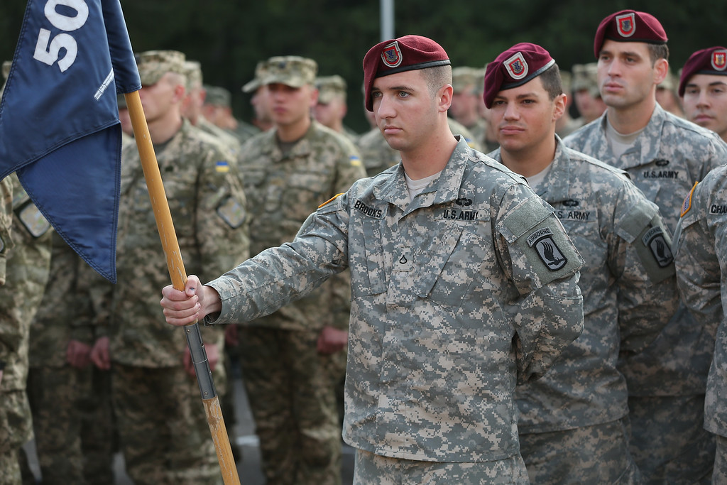 ". Ukrainian soldiers (L) and members of the U.S. Army 173rd Airborne Brigade arrive for the opening ceremony of the ""Rapid Trident\"" NATO military exercises on September 15, 2014 near Yavorov, Ukraine. (Photo by Sean Gallup/Getty Images)"
