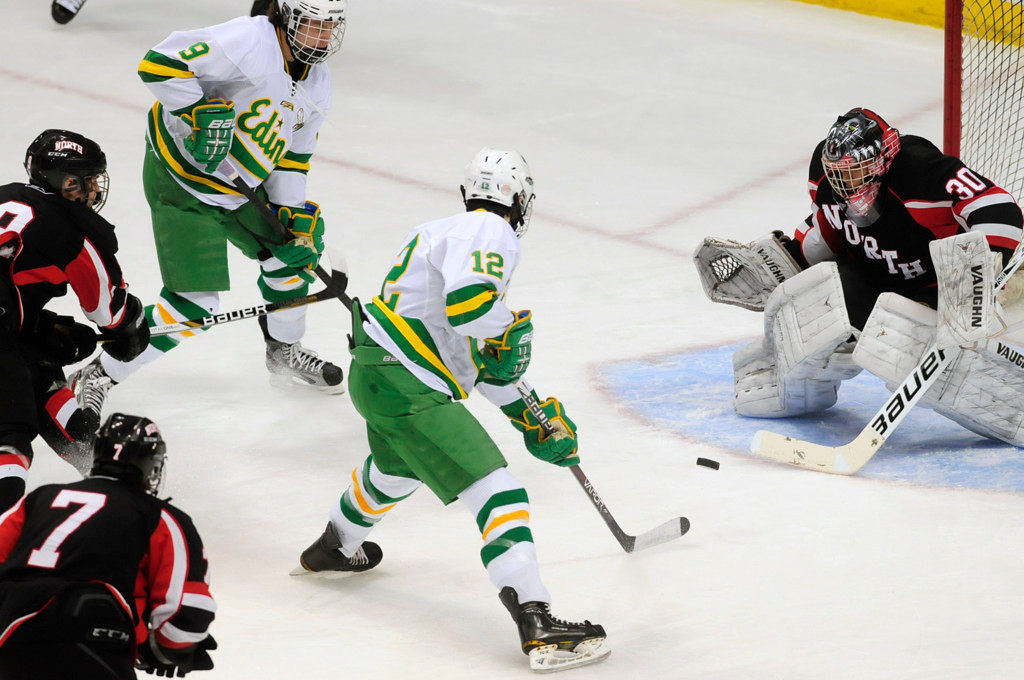 . Lakeville North goalie Will DuPont deflects a first-period shot as Edina\'s Miguel Fidler, center, and Cullen Munson gauge the rebound.  (Pioneer Press: Scott Takushi)