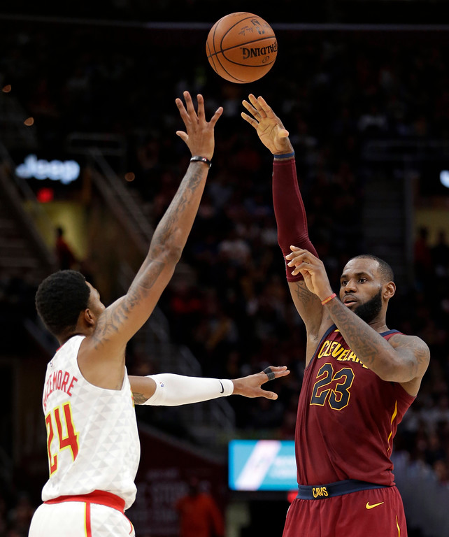 . Cleveland Cavaliers\' LeBron James (23) passes over Atlanta Hawks\' Kent Bazemore (24) in the second half of an NBA basketball game, Sunday, Nov. 5, 2017, in Cleveland. (AP Photo/Tony Dejak)