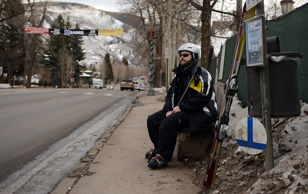 . ASPEN, CO. - JANUARY 24:  The 2013. Winter X Games officially kicked off in Aspen. Dan Baptist, who is visiting Aspen during the X Games waits for a bus, January 24, 2013,in downtown Aspen. (Photo By RJ Sangosti / The Denver Post)