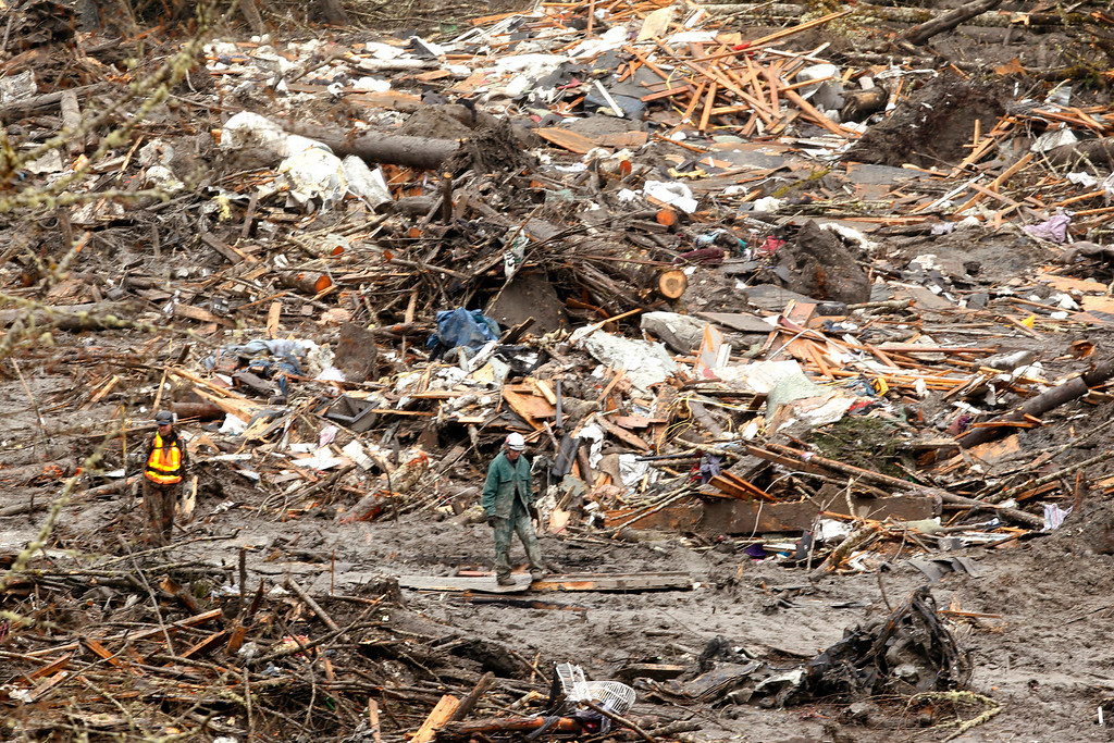 . Searchers walk on plywood boards put in to create a pathway through a massive pile of debris at the scene of a deadly mudslide, Thursday, March 27, 2014, in Oso, Wash.  (AP Photo/The Herald, Mark Mulligan, Pool)