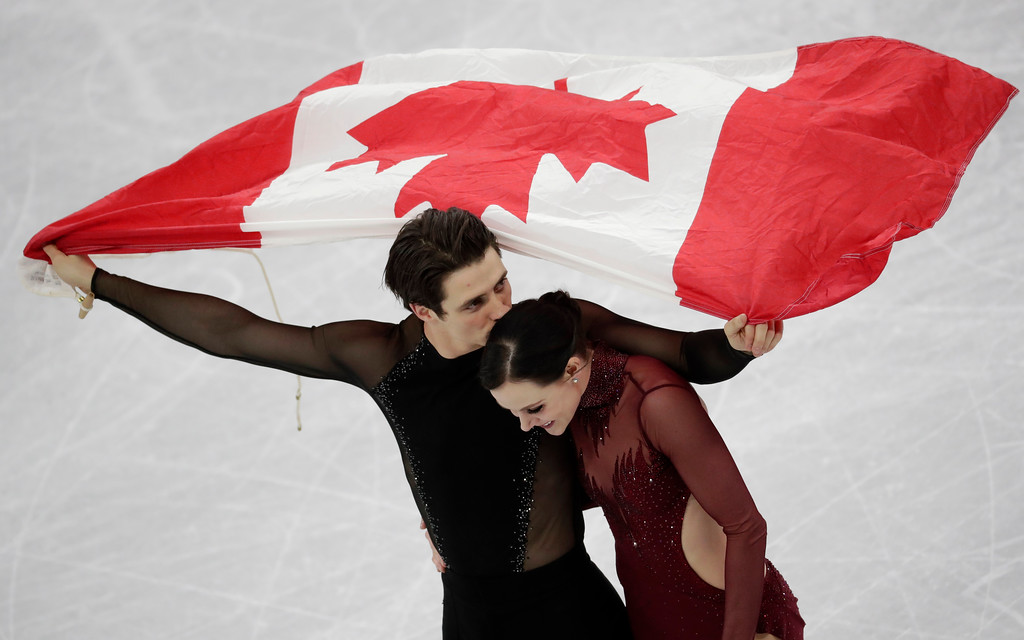 . Tessa Virtue and Scott Moir of Canada celebrate during the venue ceremony after winning the ice dance, free dance figure skating final in the Gangneung Ice Arena at the 2018 Winter Olympics in Gangneung, South Korea, Tuesday, Feb. 20, 2018. (AP Photo/Bernat Armangue)