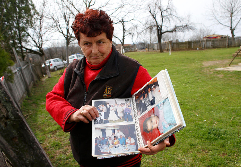. A local resident shows an album with photographs of people living in the village of Velika Ivanca, about 40 km (25 miles) southwest of Belgrade April 9, 2013. A gunman shot dead 13 people, including his mother and son, in an early-morning rampage through a small Serbian village southwest of the capital Belgrade on Tuesday, authorities said. Those killed included a two-year-old child. The gunman, identified by police as Ljubisa Bogdanovic - a war veteran born in 1953 - also shot his wife before turning the gun on himself. Both were in critical condition in hospital, police said.      REUTERS/Marko Djurica