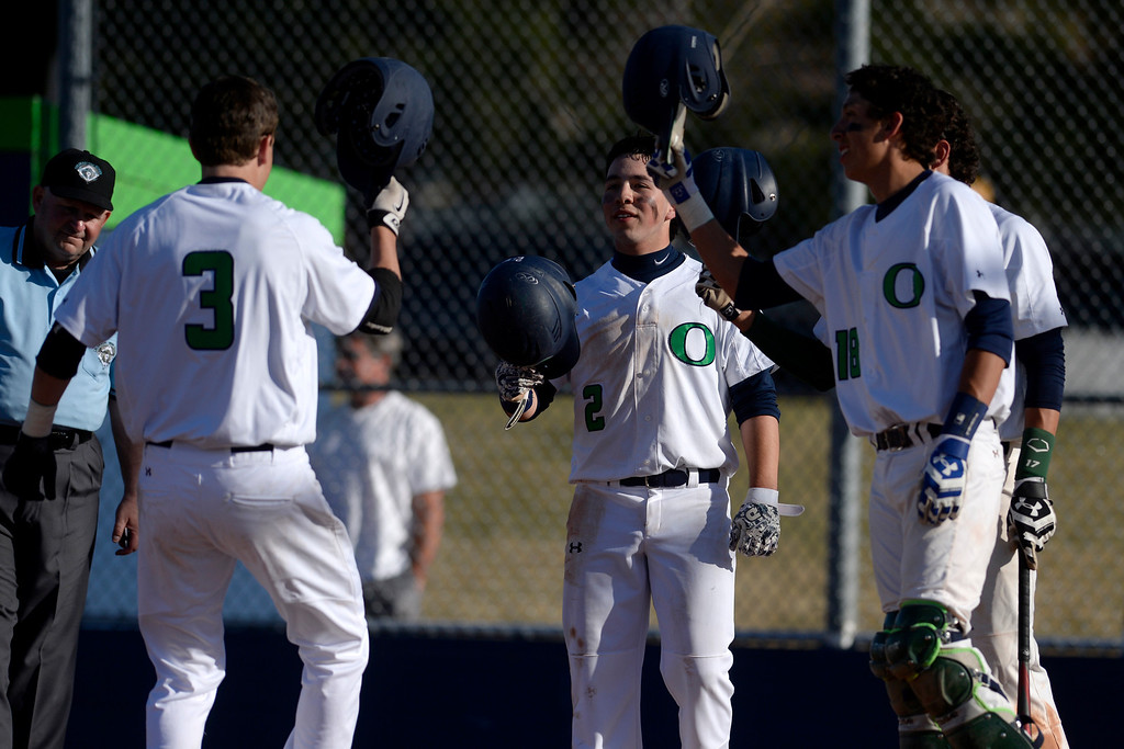 . Aurora, CO - APRIL 08: Joe Slocum (3) of the Overland Trailblazers is greeted at home by teammates Dario Villagomez (2), Joseph Sanchez (18) and Jonathan Sanchez (17) after hitting a game-tying, three-run home run off of Cody Wood (4) of the Cherry Creek Bruins. Overland hosted Cherry Creek on Tuesday, April 8, 2014. (Photo by AAron Ontiveroz/The Denver Post)