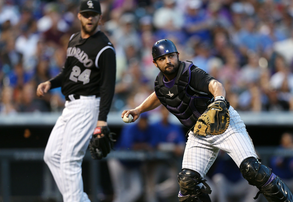 . Colorado Rockies catcher Michael McKenry, front, throws to first base to put out Chicago Cubs\' Jake Arrieta as Rockies starting pitcher Jordan Lyles watches during the fifth inning of the Rockies\' 13-4 victory in a baseball game in Denver on Wednesday, Aug. 6, 2014. (AP Photo/David Zalubowski)