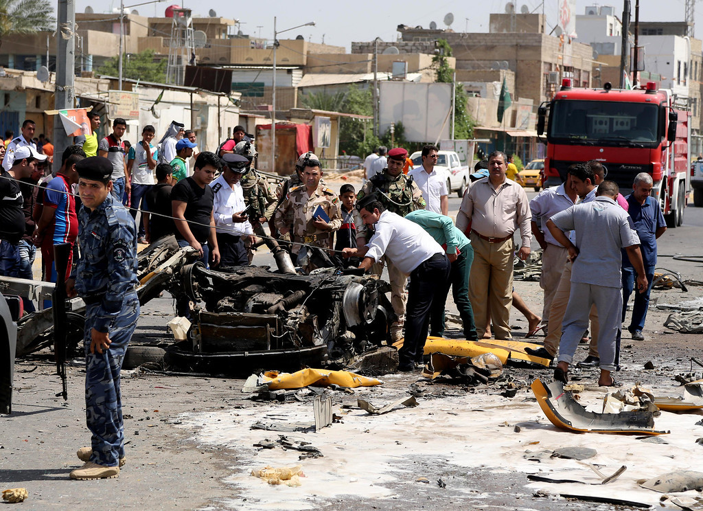 . Security forces and civilians inspect the site of a car bomb explosion in the Shiite stronghold of Sadr City, in Baghdad, Iraq, Tuesday, May 13, 2014.  (AP Photo/Karim Kadim)