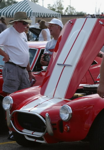 Description of . Mike Plunkette,left, of Indian chats with Larry Scholle of Ohio and owner of the red 1965 Ford Cobra on display in the Phoenix Center parking in downtown Pontiac during Saturday's Annual 2002 Woodward Dream Cruise. The annual follows Woodward Ave in Pontiac to Detroit for a 16 mile loop which attracts 1.6 million people and 30,000 muscle, street, custom and collector vehicles.