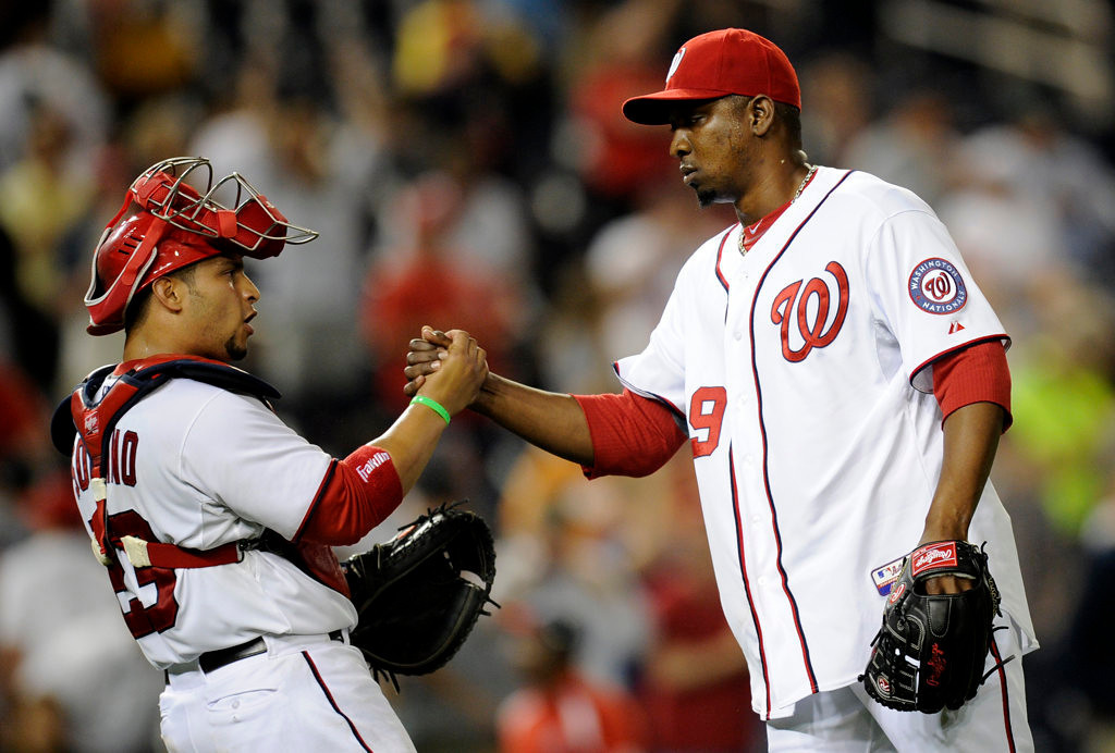 . Washington Nationals relief pitcher Rafael Soriano, right, celebrates the 5-4 win over the Minnesota Twins with teammate catcher Jhonatan Solano, left, in the second baseball game of a day-night interleague doubleheader, Sunday, June 9, 2013, in Washington. (AP Photo/Nick Wass)