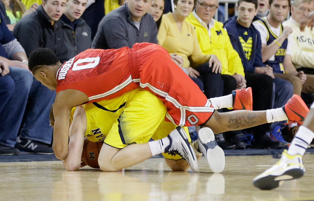 . Ohio State guard D\'Angelo Russell (0) falls on top of Michigan guard Spike Albrecht during the first half of an NCAA college basketball game, Sunday, Feb. 22, 2015, in Ann Arbor, Mich. (AP Photo/Carlos Osorio)