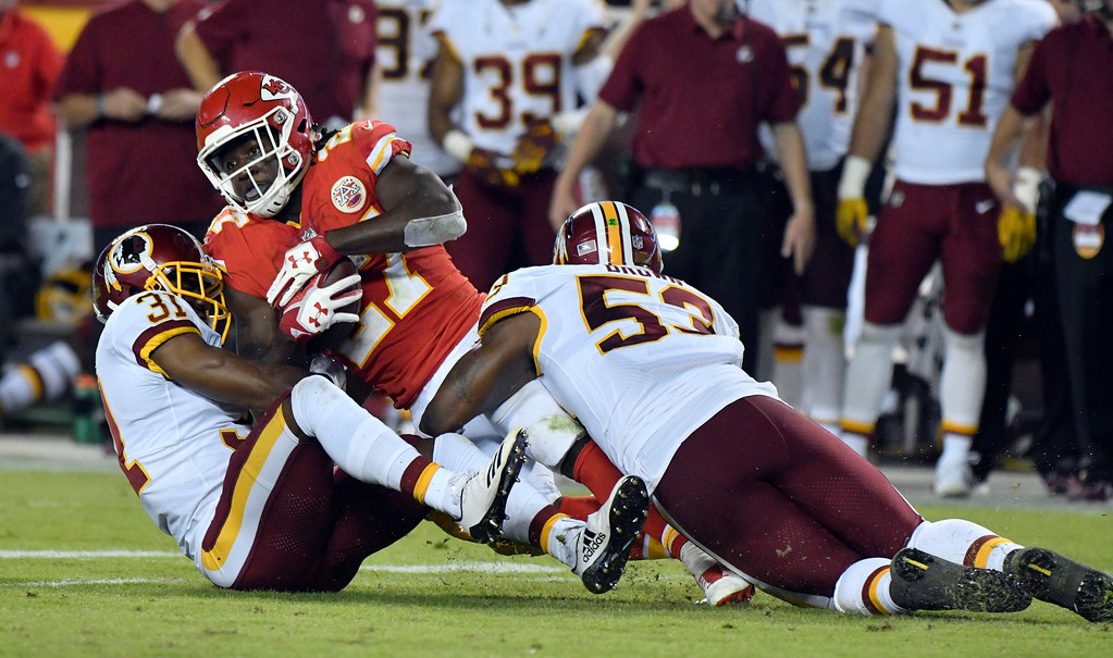 . Kansas City Chiefs running back Kareem Hunt (27) is brought down by Washington Redskins linebacker Zach Brown (53) and cornerback Fabian Moreau (31) during the second half of an NFL football game in Kansas City, Mo., Monday, Oct. 2, 2017. (AP Photo/Ed Zurga)