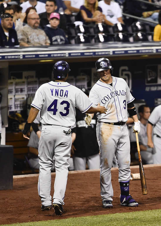 . SAN DIEGO, CA - SEPTEMBER 23:  Rafael Ynoa #43 of the Colorado Rockies, left, is congratulated by Michael Cuddyer #3 after scoring during the third inning of a baseball game against the San Diego Padres at Petco Park September, 23, 2014 in San Diego, California.  (Photo by Denis Poroy/Getty Images)