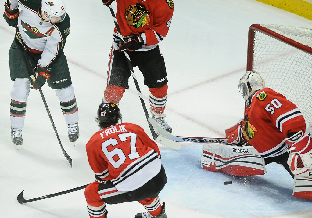 . Minnesota left wing Zach Parise, left, takes a shot on goal but is blocked by Chicago goalie Corey Crawford in the first period.  In the foreground is Chicago center Michael Frolik. (Pioneer Press: Ben Garvin)
