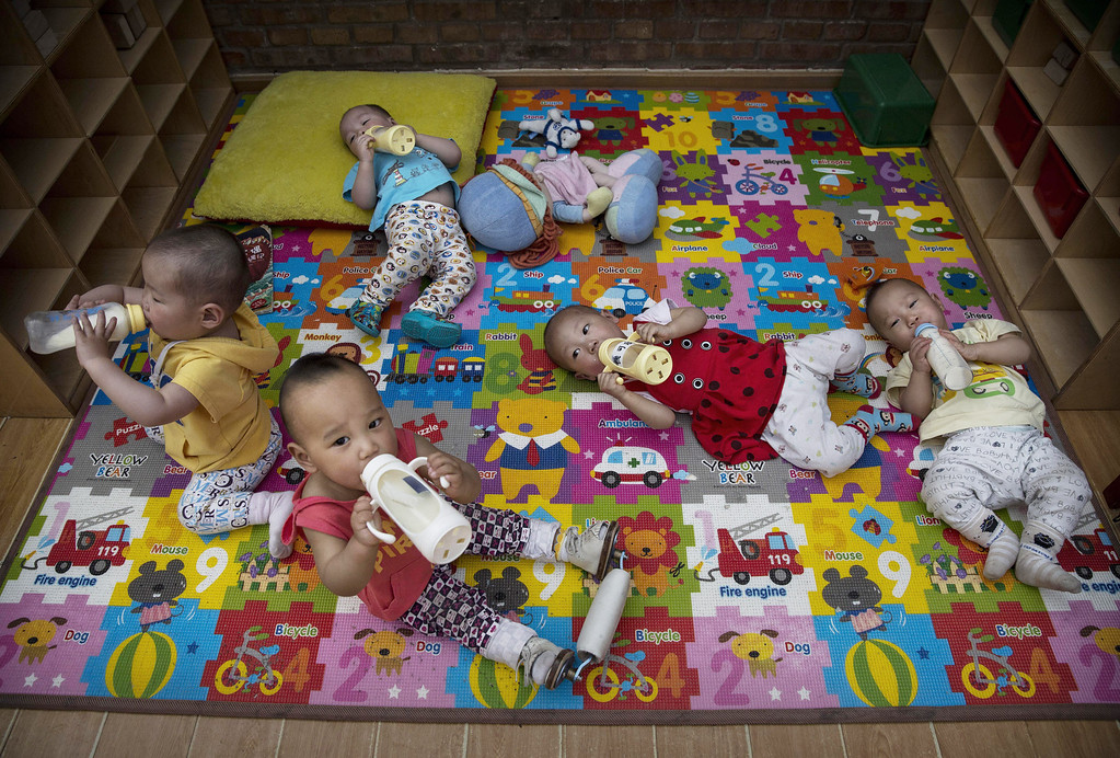 . Young orphaned Chinese children drink milk fro bottles at a foster care center on April 2, 2014 in Beijing, China.  (Photo by Kevin Frayer/Getty Images)