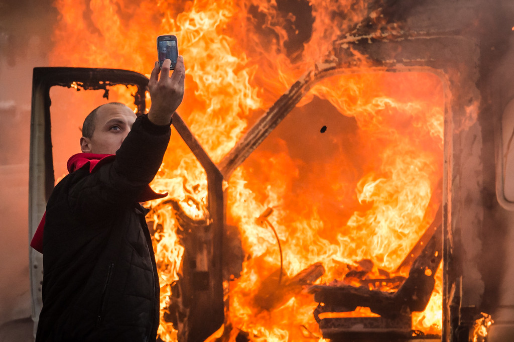 . A protestor makes a selfie in front of a burning car during a national trade union demonstration in Brussels, Thursday Nov. 6, 2014. (AP Photo/Geert Vanden Wijngaert)