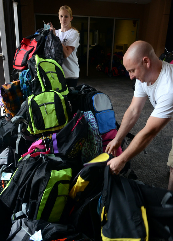 . Stuff the Bus Committee members Gioa Freed and Dave MacFarland stack  backpacks for the North Penn United Way\'s annual School Supply Drive at Penndale Middle School on Wednesday morning August 6,2014. Photo by Ann Cornell/The Reporter
