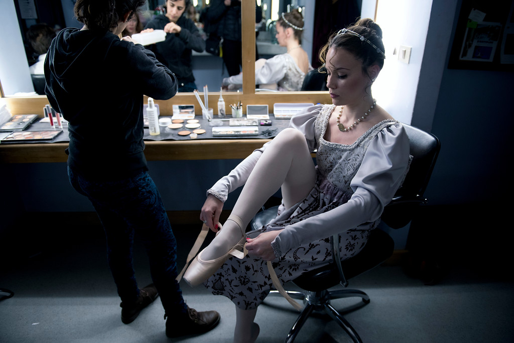 . In this Friday, Sept. 15, 2017 photo, a dancer puts her ballet shoes on before a dress rehearsal for Romeo and Juliet in Montevideo, Uruguay. About 70 professional dancers in the Uruguayan capital train under the eye of a man who wants to turn the ballet company of this small South American nation into one of the best in the world. (AP Photo/Matilde Campodonico)