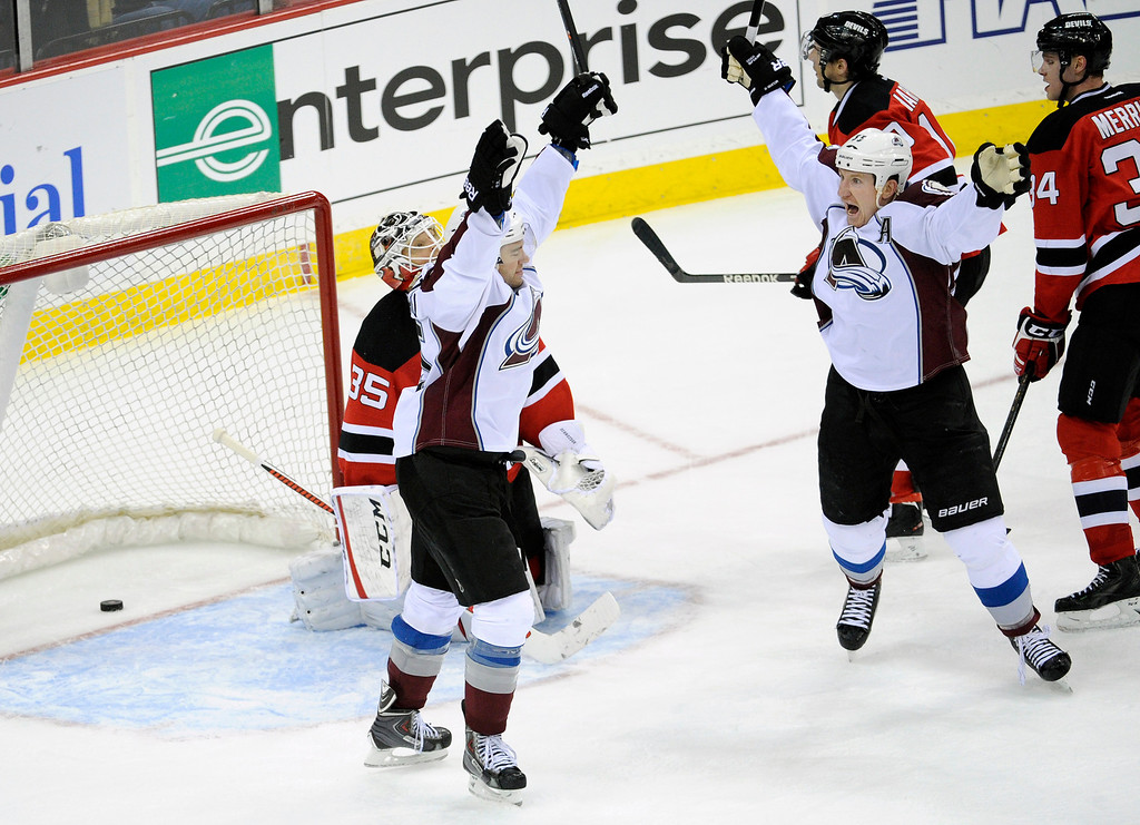 . Colorado Avalanche\'s P.A. Parenteau, left, celebrates with Cody McLeod (55) after Parenteau scored, as New Jersey Devils goaltender Cory Schneider (35), Peter Harrold and Jon Merrill, right, react during the third period of an NHL hockey game, Monday, Feb. 3, 2014, in Newark, N.J. The Avalanche defeated the Devils 2-1 in overtime. (AP Photo/Bill Kostroun)