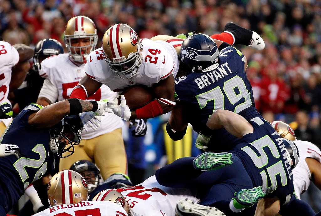 . Running back Anthony Dixon #24 of the San Francisco 49ers dives into the endzone against defensive end Red Bryant #79 of the Seattle Seahawks to score a one-yard touchdown in the first half against the Seattle Seahawks during the 2014 NFC Championship at CenturyLink Field on January 19, 2014 in Seattle, Washington.  (Photo by Otto Greule Jr/Getty Images)