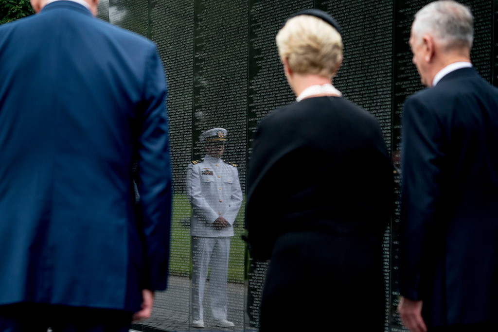 . Navy Lt. Jack McCain, the son of, Sen. John McCain, R-Ariz., is reflected in the wall of the Vietnam Memorial as Jack\'s mother, Cindy McCain, accompanied by Defense Secretary Jim Mattis, right, and President Donald Trump\'s Chief of Staff John Kelly, left, departs after laying a wreath at the Vietnam Veterans Memorial in Washington, Saturday, Sept. 1, 2018, during a funeral procession to carry the casket of her husband from the U.S. Capitol to National Cathedral for a Memorial Service. McCain served as a Navy pilot during the Vietnam War and was a prisoner of war for more than five years. (AP Photo/Andrew Harnik, Pool)