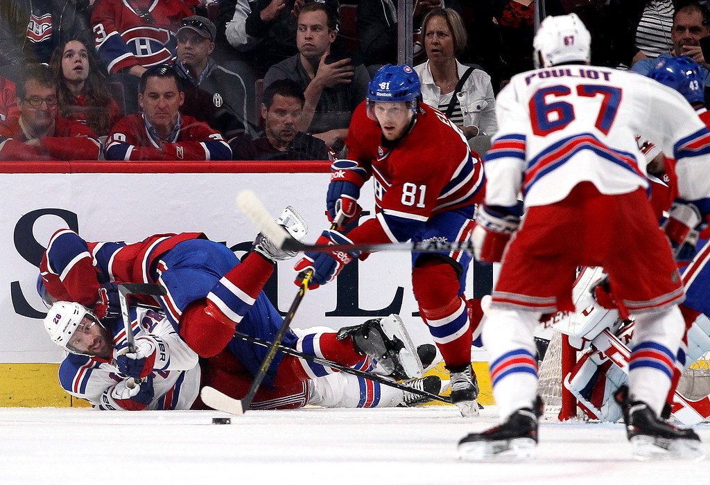 . MONTREAL, QC - MAY 17:  Dominic Moore #28 of the New York Rangers goes after the puck as P.K. Subban #76 of the Montreal Canadiens checks him into the boards in the first period in Game One of the Eastern Conference Finals of the 2014 NHL Stanley Cup Playoffs at the Bell Centre on May 17, 2014 in Montreal, Canada.  (Photo by Bruce Bennett/Getty Images)