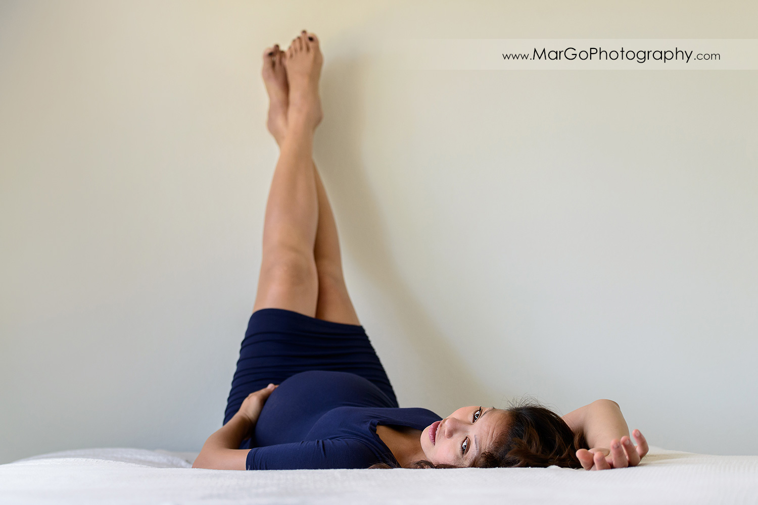 pregnant woman in navy blue dress laying on white bed and holding legs up