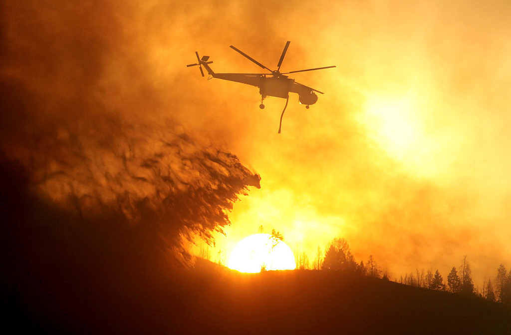 . A helicopter makes a drop while battling the Beaver Creek Fire on Saturday, Aug. 17, 2013 north of Hailey, Idaho.(AP Photo/Times-News, Ashley Smith)
