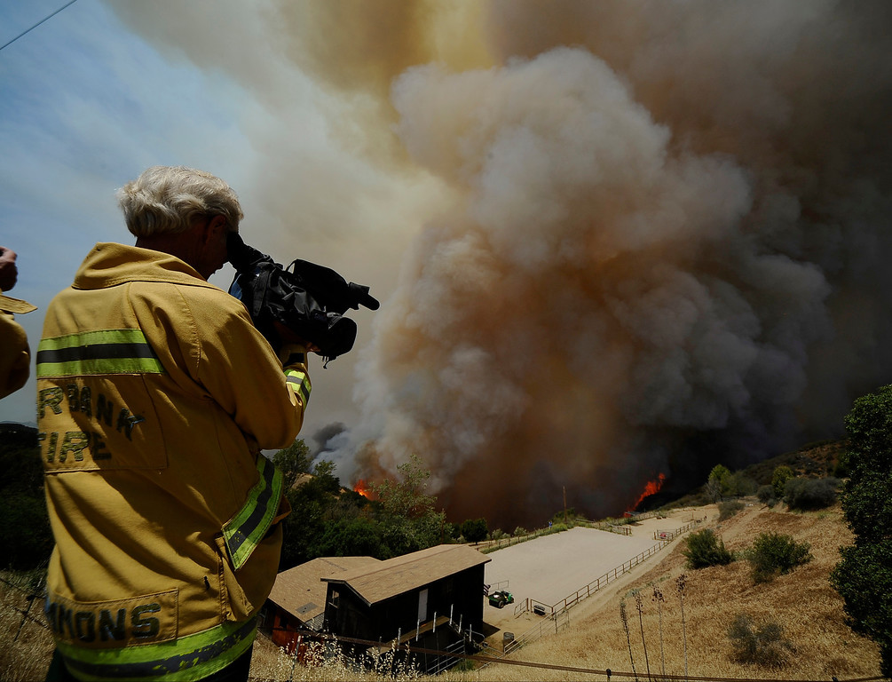 . Fire video photographer Al Simmons shoots video of fire and smoke during the second day of the Springs Fire in the mountain areas of Ventura County CA.  May 3, 2013. A fierce, wind-whipped brush fire spread on Friday along the California coast northwest of Los Angeles, threatening several thousand homes and a military base as more than 1,100 dwellings were ordered evacuated and a university campus was closed. May 2,2013. Ventura County California.  Photo by Gene Blevins/LA Daily News