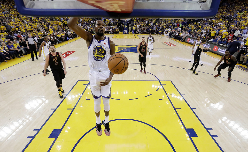 . Golden State Warriors\' Kevin Durant, center, dunks against the Cleveland Cavaliers during the second half of Game 1 of basketball\'s NBA Finals Thursday, May 31, 2018, in Oakland, Calif. (AP Photo/Marcio Jose Sanchez)