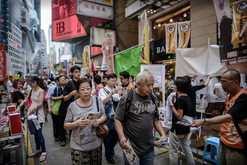 . Pedestrians get leaflets from activists in a street leading to a candlelight vigil held to mark the 24th anniversary of the 1989 crackdown at Tiananmen Square, in Hong Kong on June 4, 2013.  More than 100,000 people were expected to attend the candlelight vigil in the former British colony which is the only place in China where the brutal military intervention that ended weeks of nationwide democracy protests in 1989 is openly commemorated.  PHILIPPE LOPEZ/AFP/Getty Images