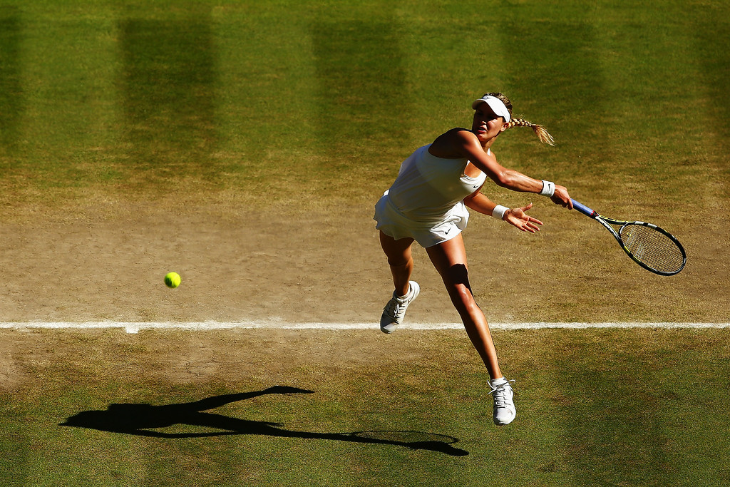 . Eugenie Bouchard of Canada leaps to play a forehand return during her Ladies\' Singles semi-final match against Simona Halep of Romania on day ten of the Wimbledon Lawn Tennis Championships at the All England Lawn Tennis and Croquet Club  on July 3, 2014 in London, England.  (Photo by Clive Brunskill/Getty Images)