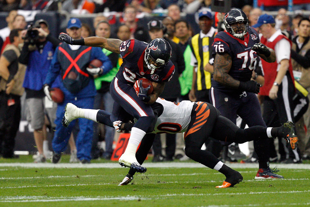 . Arian Foster #23 of the Houston Texans runs the ball against Reggie Nelson #20 of the Cincinnati Bengals during their AFC Wild Card Playoff Game at Reliant Stadium on January 5, 2013 in Houston, Texas.  (Photo by Bob Levey/Getty Images)