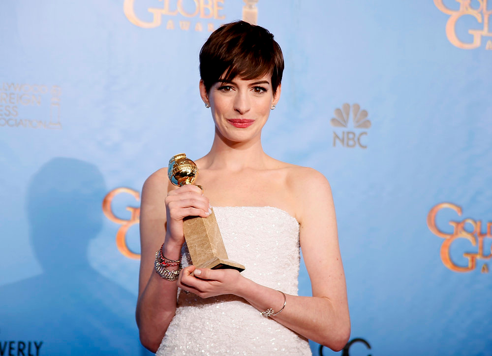 Description of . Anne Hathaway holds the award she won for Best Supporting Actress in a Motion Picture, Comedy or Musical for her work in