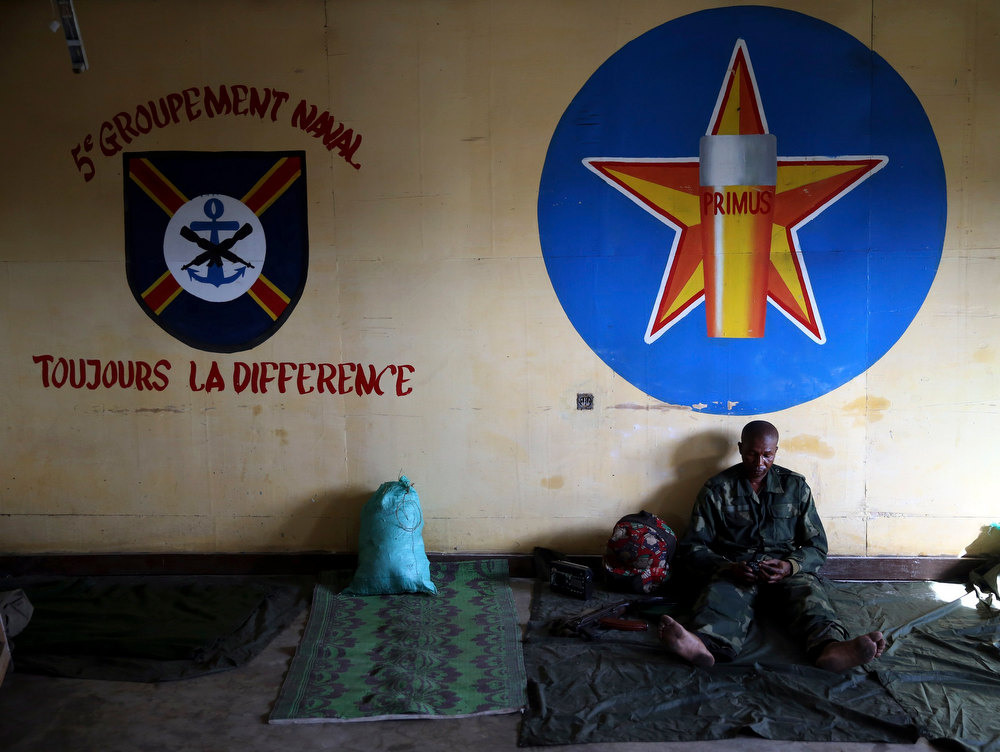 Description of . A government army FARDC soldier sits inside a building in a military base in Goma December 3, 2012. REUTERS/Goran Tomasevic