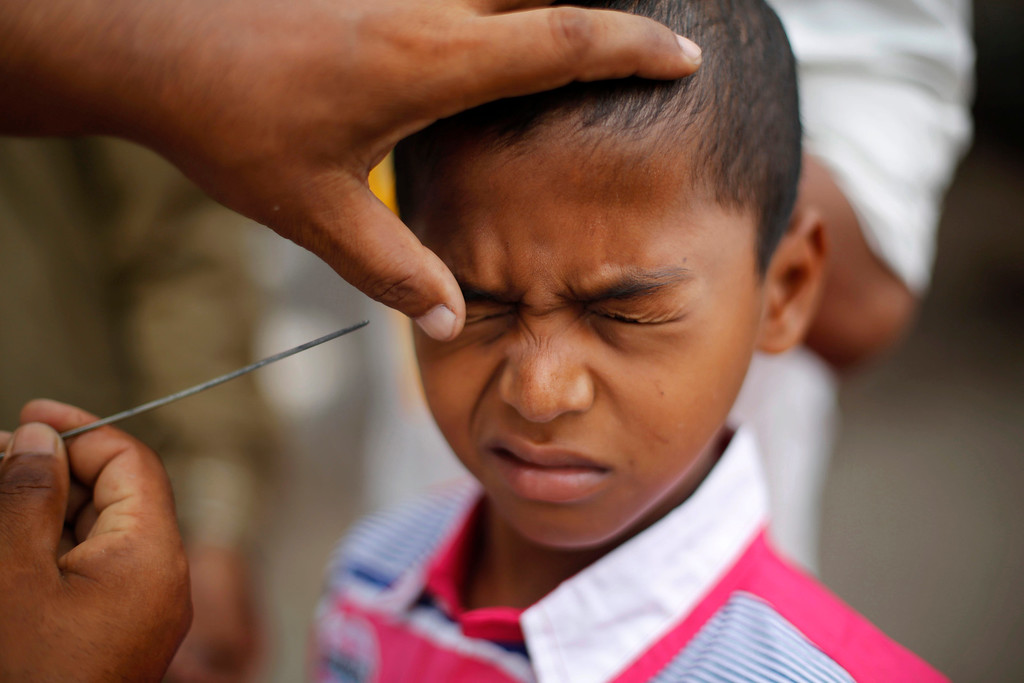 . An Indian Muslim boy reacts as a man applies Kohl, an eye cosmetic on his eye after prayers during Eid al-Adha, or the Feast of the Sacrifice, in Mumbai, India, Wednesday, Oct. 16, 2013. (AP Photo/Rafiq Maqbool)