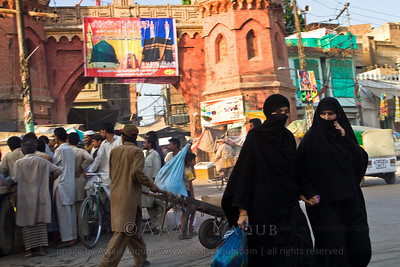 Two ladies covered in burka passing by crowd of men busy in some other thing