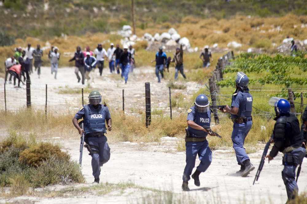 Description of . Members of the South African Police Services retreat from a group of rock-throwing striking farmworkers during violent clashes, on January 10, 2012 in de Doorns, a small farming town about 140Km North of Cape Town, South Africa. The farm workers have said that they they will not return to work on the fruit growing region's farms until they receive a daily wage of at least R150($17) per day, which is about double what they currently earn.  AFP PHOTO / RODGER BOSCH/AFP/Getty Images