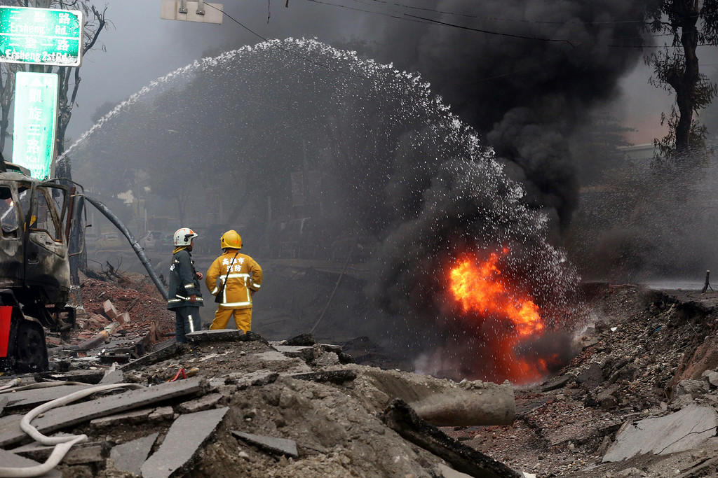 . Firemen put out fire on the part of a destroyed street as fire continue to burn following multiple explosions from an underground gas leak in Kaohsiung, Taiwan, early Friday, Aug. 1, 2014. Scores of people were killed and more than 200 others injured when several underground gas explosions ripped through Taiwan\'s second-largest city overnight, hurling concrete through the air and blasting long trenches in the streets, authorities said Friday. (AP Photo)