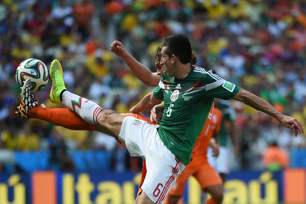 . Netherlands\' defender Daley Blind (back) vies with Mexico\'s midfielder Hector Herrera during a Round of 16 football match between Netherlands and Mexico at Castelao Stadium in Fortaleza during the 2014 FIFA World Cup on June 29, 2014.   AFP PHOTO/ YURI CORTEZ