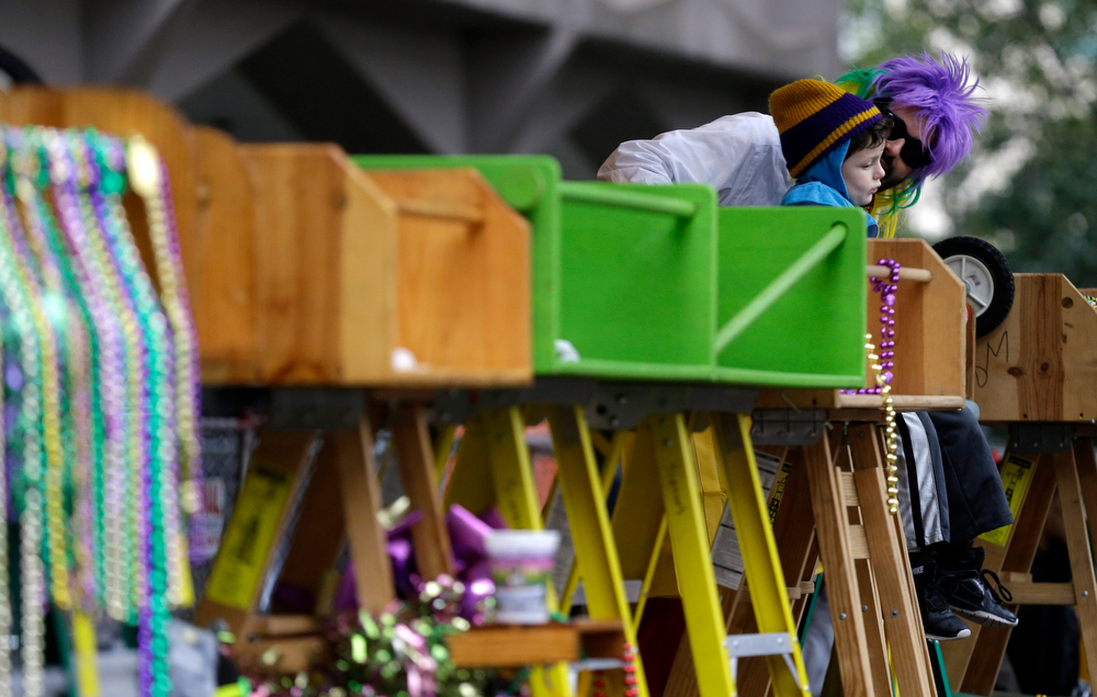 Description of . Evan Lazarof, 5, of New Orleans, sits on a child's ladder with his father Gary Lazarof, amongst ladders that would normally be filled with children, as parades roll by on St. Charles Ave. during Mardi Gras in New Orleans, Tuesday, March 4, 2014. Rain and unusually cold temperatures kept most of the normally massive and festive crowds away. (AP Photo/Gerald Herbert)