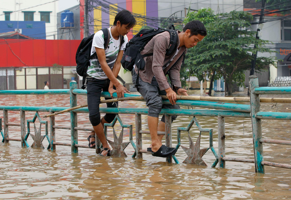 . Two men walk through a fence to cross a flooded road in Jakarta January 16, 2013. Thousands of residents are being evacuated after floods inundated several areas of Jakarta due to the overflow of the Ciliwung River and several days of heavy rains in the capital city, local media reported on Wednesday.   REUTERS/Enny Nuraheni