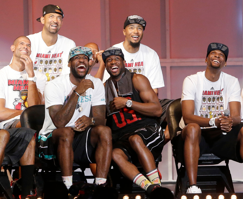 . Miami Heat players laugh as they watch highlights of center Chris Bosh, right, Monday, June 24, 2013, during a celebration for season ticket holders at the American Airlines Arena in Miami. Other players from left are: Shane Battier, Juwan Howard, LeBron James, Dwyane Wade and Rashard Lewis. The Heat defeated the San Antonio Spurs 95-88 in Game 7 to win their second straight NBA championship. (AP Photo/Wilfredo Lee)
