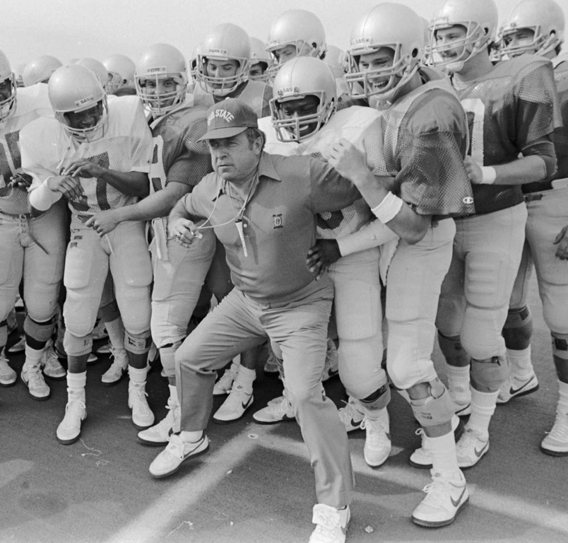 . Ohio State coach Earle Bruce pushes his players backwards behind the line on the practice field where they were beginning laps during spring practice, April 1, 1986, in Columbus, Ohio. Bruce, who was hired to replace the fired Woody Hayes, was himself fired before the Michigan game that fall. Bruce blames former Ohio State President Ed Jennings and others in the Columbus business community. Ten years later, Jennings still won\'t talk about it, saying Wednesday, Nov. 19, 1997, it\'s because of a court order. (AP Photo/Gary Gardiner, File)
