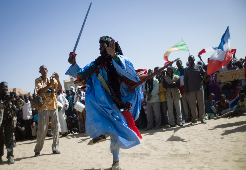 Description of . Malian people wait for the visit of French President on February 2, 2013 in Timbuktu. France\'s president Francois Hollande received a rapturous welcome today as he visited Mali to push for African troops to take over a French-led offensive that drove back Islamist rebels from the country\'s desert north. FRED DUFOUR/AFP/Getty Images