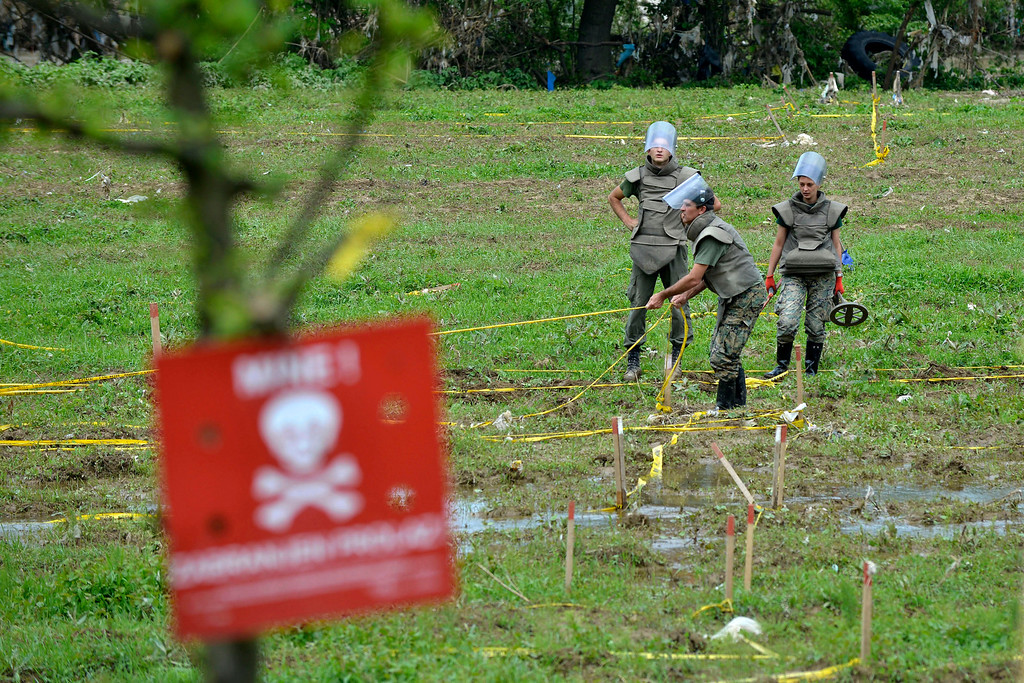 . Bosnian soldiers repair mine warning signs in fields near the banks of the river Bosnia which flooded near the town of Visoko, 30 km north of Sarajevo, Bosnia-Herzegovina on Tuesday May 20, 2014. At least two dozen people have died and tens of thousands of people have been forced from their homes. But in addition to the usual dangers, the flooding has unearthed land mines left over from Bosnia\'s 1992-95 war and washed away the signs that marked them. (AP Photo/Sulejman Omerbasic)