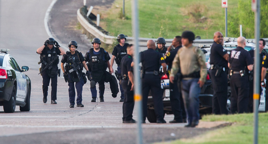 . Dallas SWAT  and other police officers gather at the intersection of Interstate 45 and E Palestine Street, where police have cornered a suspect in a van on Saturday, June 13, 2015 in Hutchins, Texas.   Police Chief David Brown says a police sniper has shot the suspect in an overnight attack on police headquarters and that the department is checking to see if he\'s still alive. Brown says investigators believe the man acted alone in the early-morning attack on Dallas police headquarters, despite early witness reports that others may have taken part.    (Ashley Landis/The Dallas Morning News via AP)
