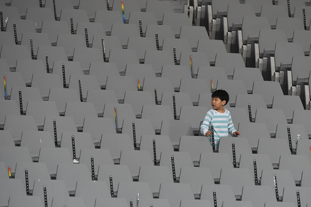. A young child runs among empty seating during athletic events of the 17th Asian Games at the Incheon Asiad Main Stadium in Incheon on September 27, 2014.  PHILIPPE LOPEZ/AFP/Getty Images