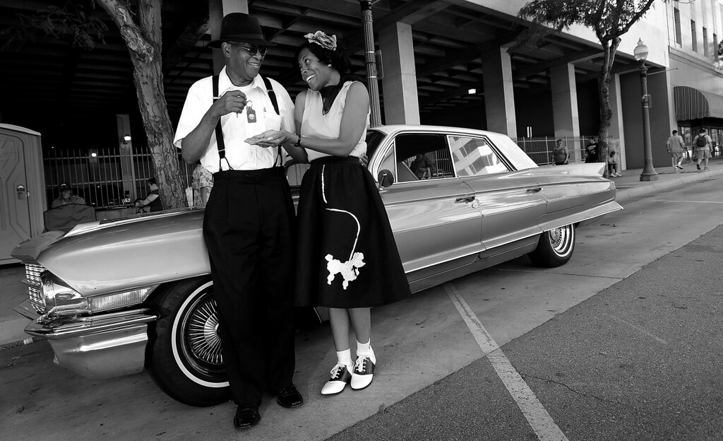 ". ""Papa\'s Got A Brand New Bag\""--Joseph Sanford, of Corona, jokes with daughter Dia Poole, of Sacramento, along E Street in downtown San Bernardino September 14, 2012.  They stand in front of Sanford\'s 1962 Cadillac Sedan Deville.  \""Its just a good time to come out and spend some quality time with my dad,\"" says Poole of their annual date at the Route.  \""Who knows one of these days he just might give me those keys.\""  (Photo by Gabriel Luis Acosta/The Sun)"