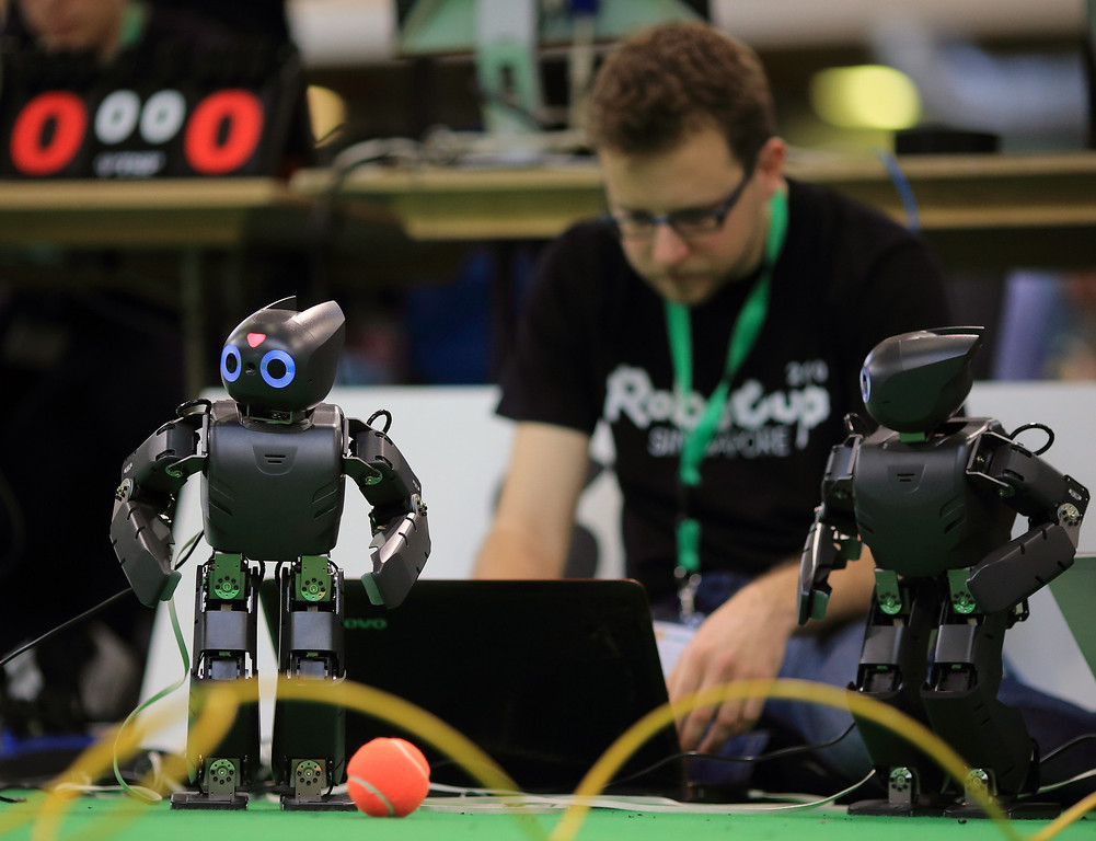 """. A technicians configures robots for a match during the \""""RoboCup German Open 2013\"""" in Magdeburg, eastern Germany on April 26, 2013. The 4th edition of RoboCup German Open 2013 takes place from April 26-28 and is attended by  43 international RoboCup Major League teams from 14 countries demonstrating the state-of-the-art robotics in soccer, rescue and service robots. JENS WOLF/AFP/Getty Images"""