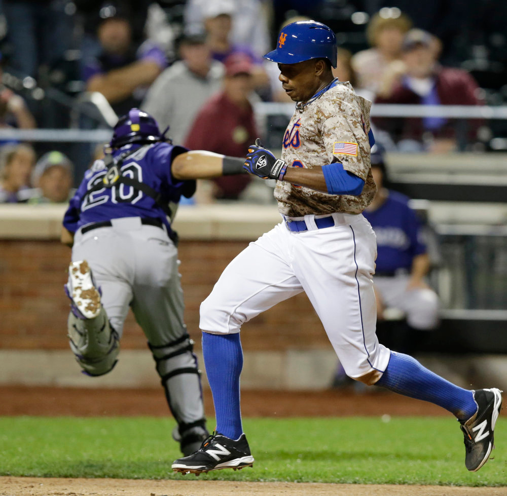 . New York Mets Curtis Granderson (3) scores on Wilmeer Flores\' s walk-off, ninth-innning, sacrifice fly in the Mets 3-2 victory over the Colorado Rockies in a baseball game in New York, Monday, Sept. 8, 2014. Colorado Rockies catcher Wilin Rosario (20) is drawn off the plate by the throw. (AP Photo/Kathy Willens)